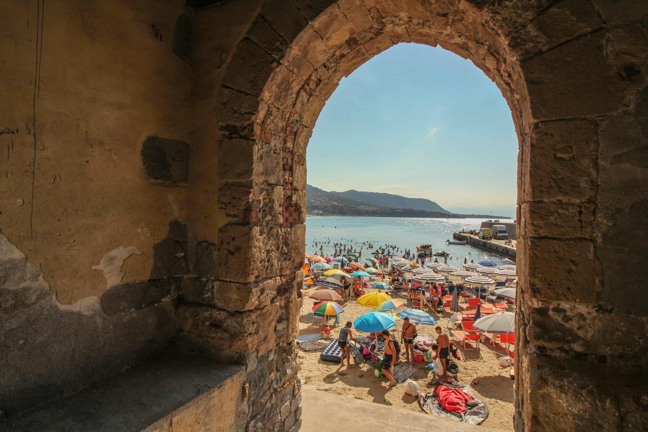 Blick durch einen Torbogen auf den Strand von Cefalù